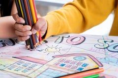 Boy hand drawing in kindergarten art classroom. Boy hand is drawing in kindergarten art classroom stock images