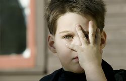 Boy with a hand in front of his face Stock Image