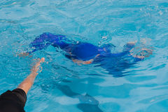 Boy hand helping drowning his brother. That going to swimming pool floor Royalty Free Stock Image