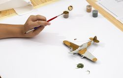 Boy hand painting plastic model kit of ww2 aircraft Stock Photo