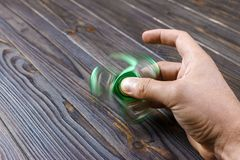 boy hand playing with fidget spinner gadget. Green hand spinner, fidgeting hand toy rotating on man hand royalty free stock photo