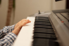 Boy hand playing the piano Stock Photo