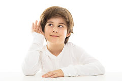 Boy with a hand to ear in a listening gesture Stock Photos