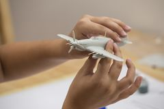 Boy hands assembling plastic model kit of ww2 aircraft. Plane at home. Hobby and leisure Stock Photography