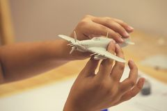 Boy hands assembling plastic model kit of ww2 aircraft 2. Boy hands assembling plastic model kit of ww2 aircraft plane at home. Hobby and leisure. Vintage style Royalty Free Stock Photo