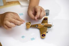 Boy hands finishing plastic model kit of ww2 aircraft Royalty Free Stock Photography
