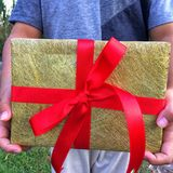 A boy hands is holding a gift box . A group of wrapped gift boxes for someone special in greeting moments. They're decorating with red satin ribbon. For royalty free stock images
