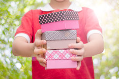 Boy hands holding and giving gift boxes Royalty Free Stock Photography