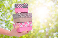 Boy hands holding and giving gift boxes Royalty Free Stock Photo