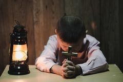 Boy hands holding a holy cross praying to God In the dark and with the lamp beside, Child Praying for God Religion royalty free stock photo