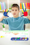 Boy with hands painted in colorful paints ready for hand prints. Happy boy with painted hands at home royalty free stock image