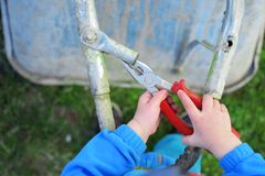 Boy hands repair wheelbarrow. Little two years old boy hands learning to repair grey old metal wheelbarrow with red pliers on grass background outdoors top view stock photo