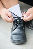 Boy hands tie shoelaces by himself Royalty Free Stock Photos