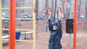 Boy hang on gymnastic rings in the courtyard of the city house on the Playground. Boy hang on gymnastic rings in the courtyard of the city house on the stock video