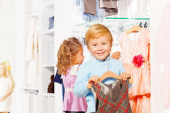 Boy with hanger and girl behind choosing clothes Royalty Free Stock Photography