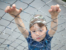 Boy hanging on the bars. Caucasian boy hanging on the bars outdoor Stock Image