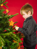 Boy hanging Christmas tree decorations Stock Images