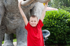Boy hanging on elephant tusks sculpture Royalty Free Stock Photo