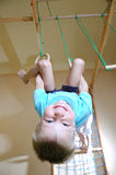 Boy hanging on gymnastic rings Royalty Free Stock Images
