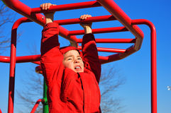 Boy Hanging on Monkey Bars. A young boy in a red coat struggles to make it across the red monkey bars stock photography