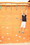 Boy hanging on obstacle course Stock Image