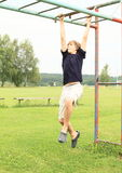 Boy hanging on obstacle course. Little boy - strong kid hanging on obstacle course royalty free stock photos