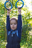 Boy hanging on the rings Royalty Free Stock Images