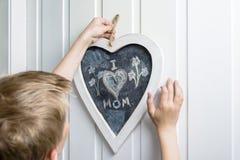 Boy hanging up a heart shaped blackboard Royalty Free Stock Photos