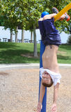 Boy hanging upside down in park Royalty Free Stock Photography