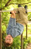 Boy hangs on bars headfirst Royalty Free Stock Images