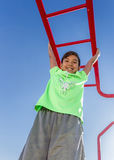 Boy hangs from bars. A boy hangs from the monkey bars on a bright summer day Royalty Free Stock Photography
