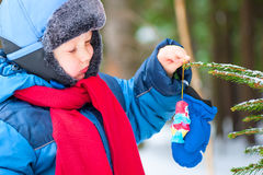 Boy hangs on the Christmas tree decoration Royalty Free Stock Image