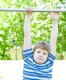 Boy hangs on a horizontal bar Stock Photo
