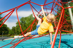 Boy hangs with legs and arms hold the ropes Royalty Free Stock Photo