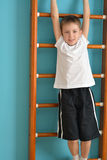 Boy hangs off the ladder Royalty Free Stock Photo