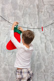 Boy hangs socks for Santa Claus. Stock Image
