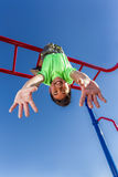 Boy hangs upside down while playing. Royalty Free Stock Image