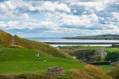 A boy happily playing football near Tynemouth Priory and Castle. royalty free stock photos