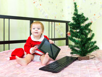 Boy is happy to get New Year present tablet computer. Near keyboard and Christmas tree Stock Photography