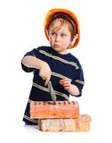 Boy in hard hat with brick Stock Images