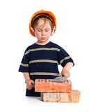 Boy in hard hat with brick Stock Image
