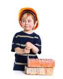 Boy in hard hat with brick Stock Photos