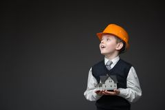 Boy in hard hat keeping home model Stock Image