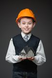 Boy in hard hat keeping house model Royalty Free Stock Image