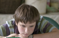 Boy hardly thinking. A boy hardly solving homework Stock Photo