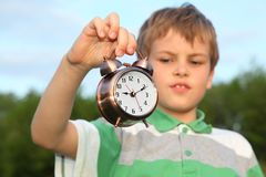 Boy has control over alarm clock, nature Royalty Free Stock Photo