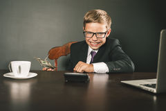 Boy has earned a lot of money. Banker holds in hand American dollars. Cunning business boy. Successful school boy. Happy. Success concept. Business suit. Stock Stock Photos