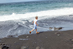 Boy has fun at the black  beach Royalty Free Stock Photo