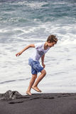 Boy has fun at the black volcanic beach Royalty Free Stock Image