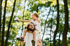 Boy has fun with father in the park on sunny day, both dressed in the white t-shirts. Boy sits on the father`s shoulders royalty free stock photo